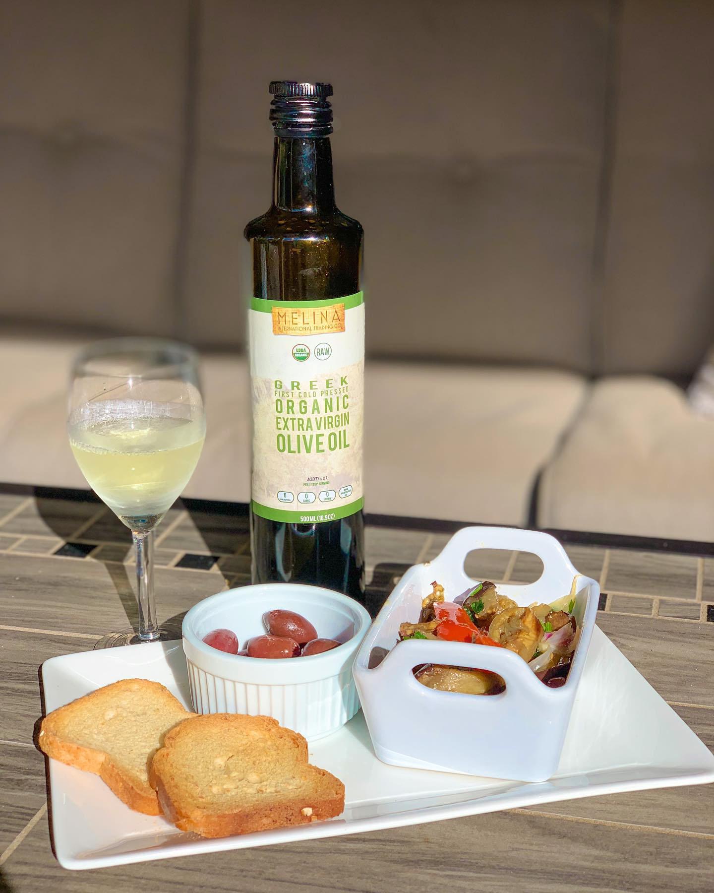 Bottle of Melina Extra Virgin Olive Oil next to olives, salad, and wine